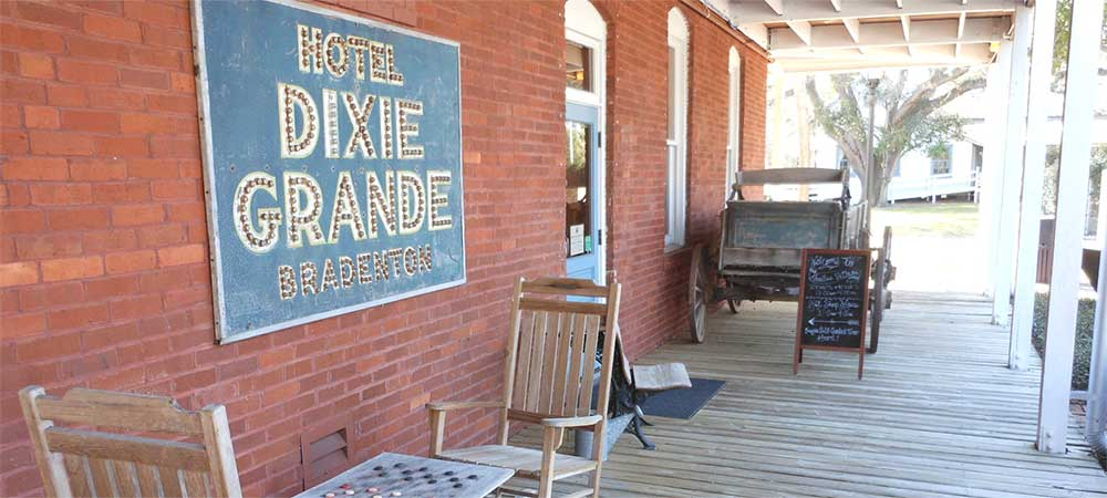 A historical patio featuring a sign from Hotel Dixie Grande Bradenton
