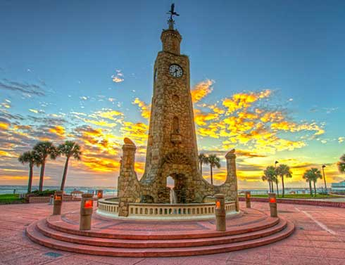 A tall coquina clock tower stands on a round platform by the ocean in Daytona Beach, Florida
