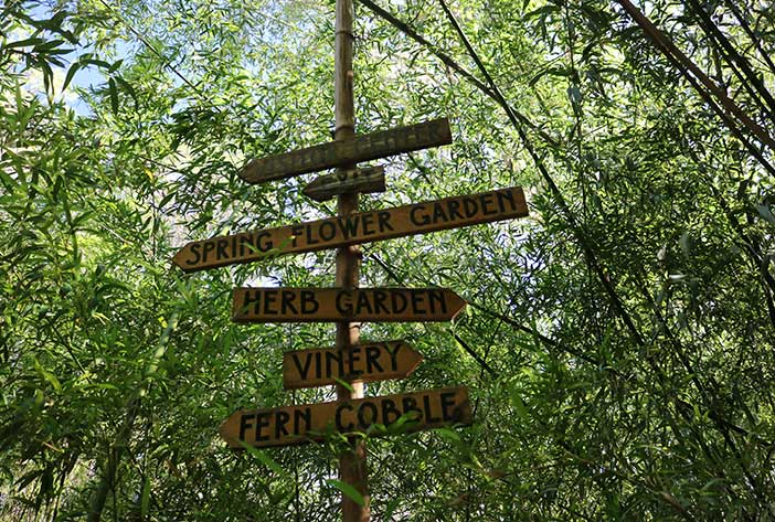 A wooden sign points toward different areas of Kanapaha Botanical Gardens