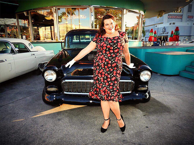 A young woman in front of a classic car at the Old Town Kissimmee Car Show in Florida