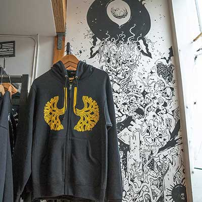 A gray sweatshirt hangs on a rack in front of a painted wall at Town Biz in Oakland, California