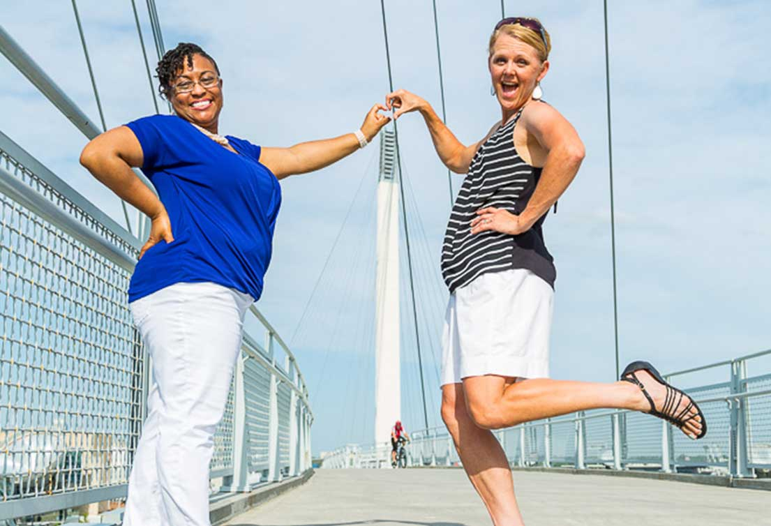 Two women stand on the Iowa-Nebraska border on Bob Kerrey Pedestrian Bridge in Omaha, Nebraska