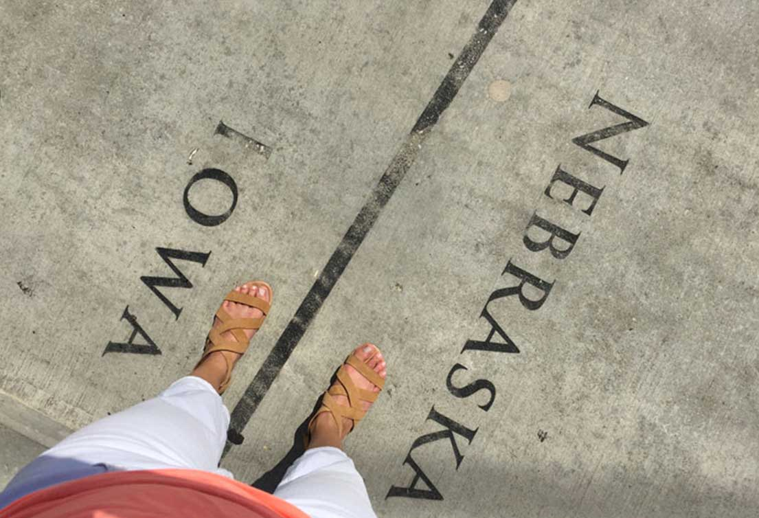 A woman wearing sandals straddles the Iowa-Nebraska border on Bob Kerrey Pedestrian Bridge in Omaha, Nebraska