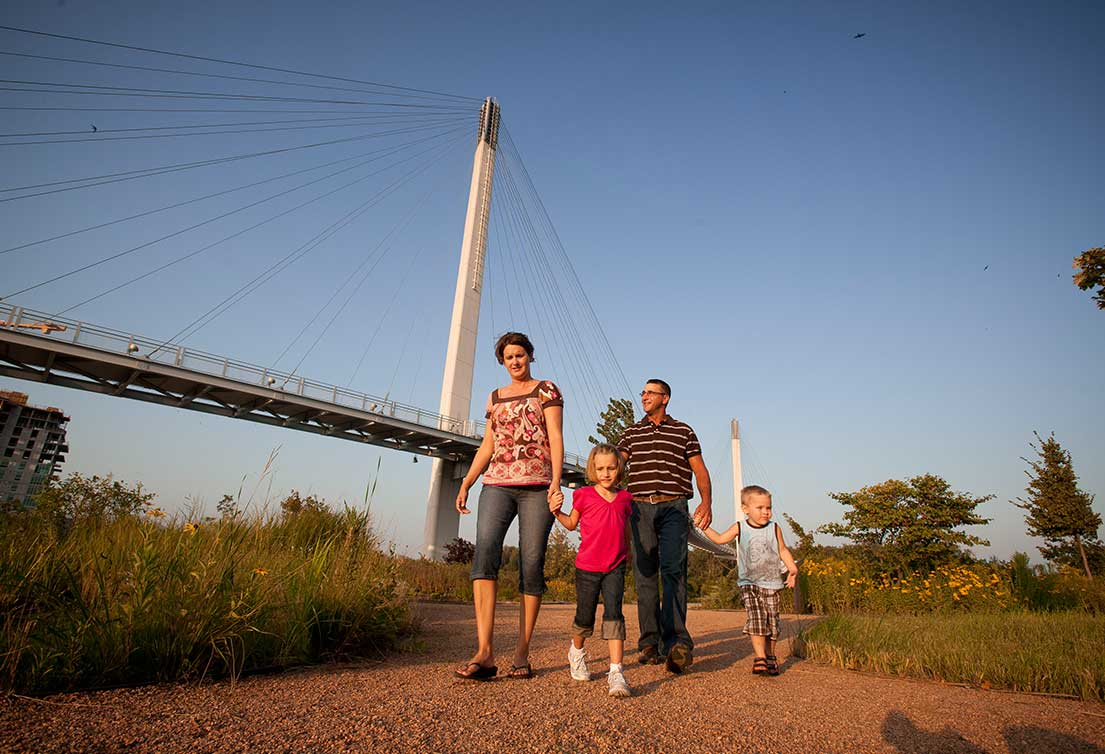 A family with two young children walk on gravel near the Bob Kerrey Pedestrian Bridge in Omaha, Nebraska