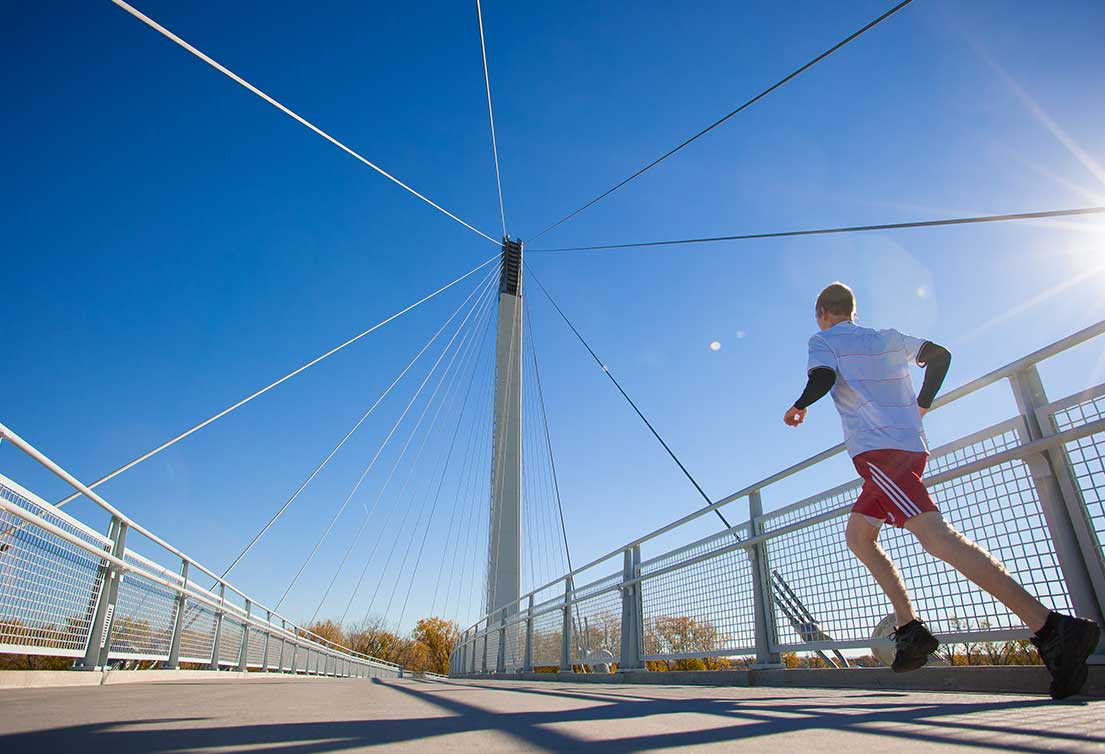 A man in red shorts runs on the Bob Kerrey Pedestrian Bridge in Omaha, Nebraska