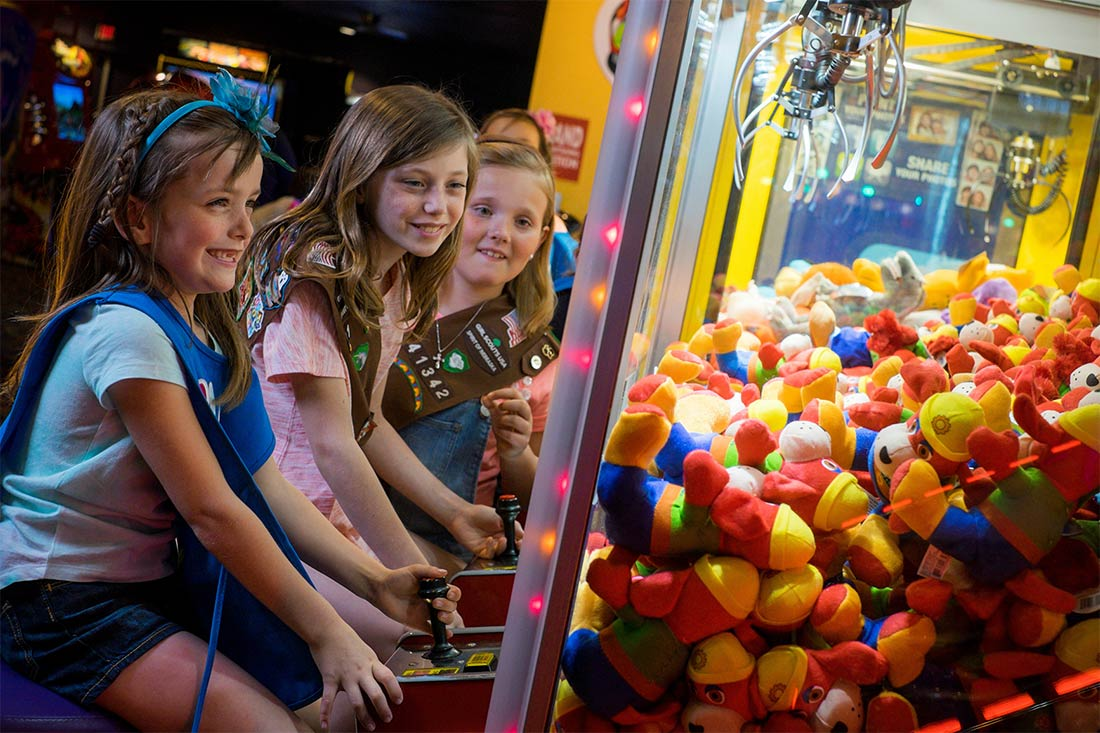 Girl Scouts playing Amazing Pizza Machine crane game in Omaha, Nebraska