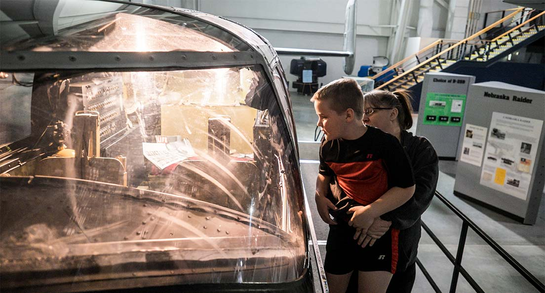 A mom lifts her son to peer into an airplane cockpit at the Strategic Air Command & Aerospace Museum in Omaha, Nebraska