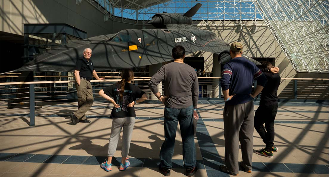A small group of museum visitors listen to a docent talk about an airplane at the Strategic Air Command & Aerospace Museum in Omaha, Nebraska