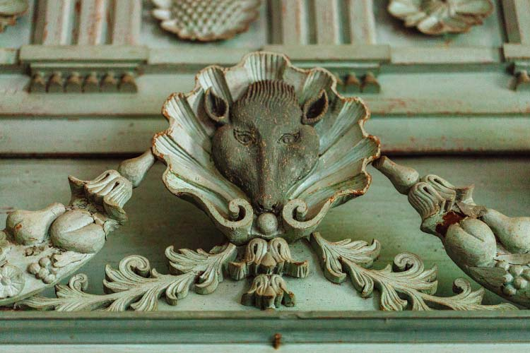 A fireplace pediment featuring a wood-carved pig in Drayton Hall in Charleston, South Carolina