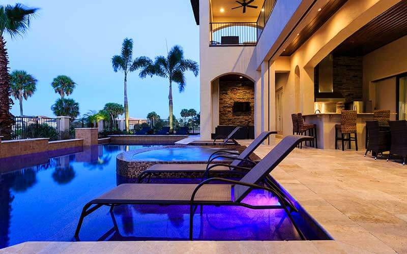 An outside pool at twilight in a Jeeves vacation home in Kissimmee, FL
