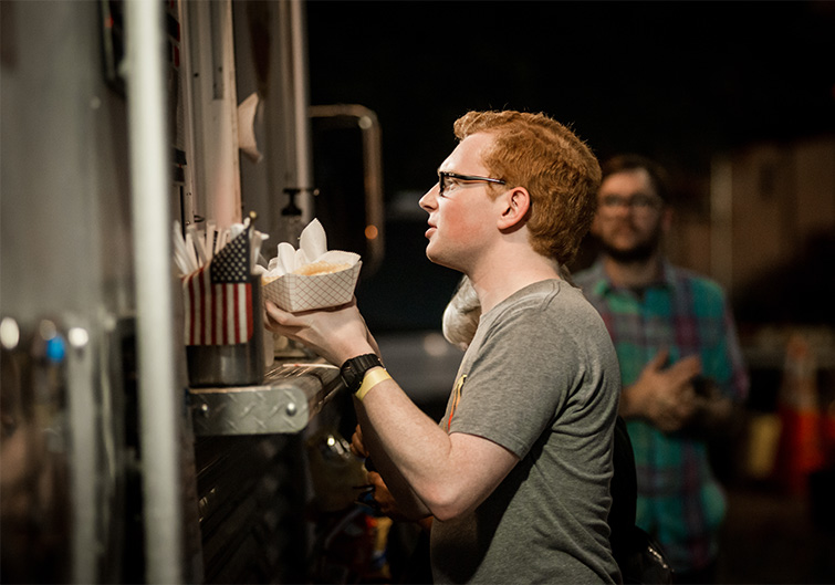 A red-haired man orders from a food truck at Railroad Square Art Park in Tallahassee, Florida