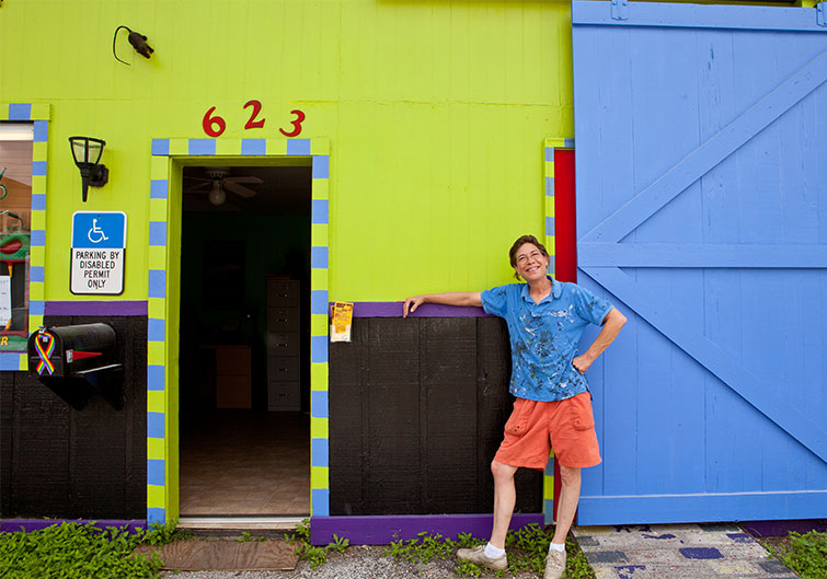 An artist stands outside of a lime green and blue doorway at Railroad Square Art Park in Tallahassee, Florida