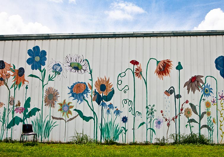 A white wall painted with colorful flowers at Railroad Square Art Park in Tallahassee, Florida