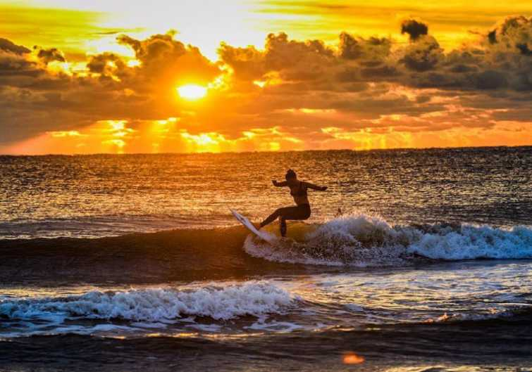 A surfer catches a wave at sunset at Jacksonville Beach, FL