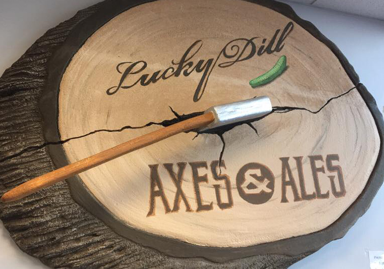 "A sign designed to look like a split trunk with an axe sticking out labeled ""Lucky Dill Axe and Ales"""