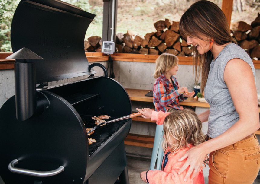 A woman helps a young child grill chicken on a barbeque while another child sits at a wooden table in the background in Bend, Oregon