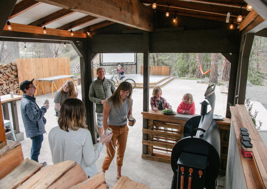 A group of adults and children talk in a covered outdoor space with a barbeque with an open patio space behind them in Bend, Oregon