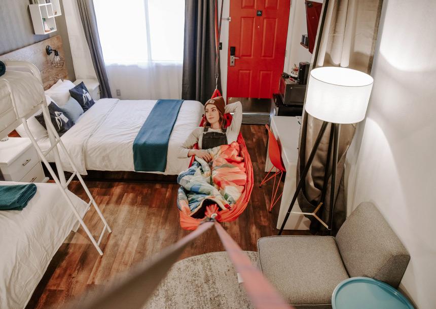 A teenage girl reclines in an orange hammock suspended in a bedroom in Bend, Oregon