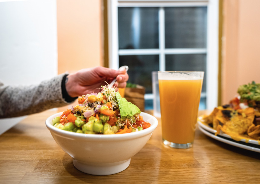 An adult hand puts a fork into a salad bowl with a glass of beer next to it in Bend, Oregon