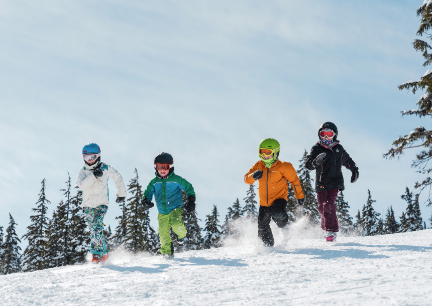 Four children in snow gear run down a snowy slope with green trees in the background in Bend, Oregon
