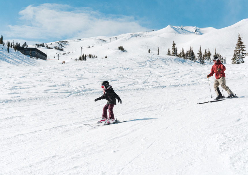 An adult and child ski down a slope in Bend, Oregon