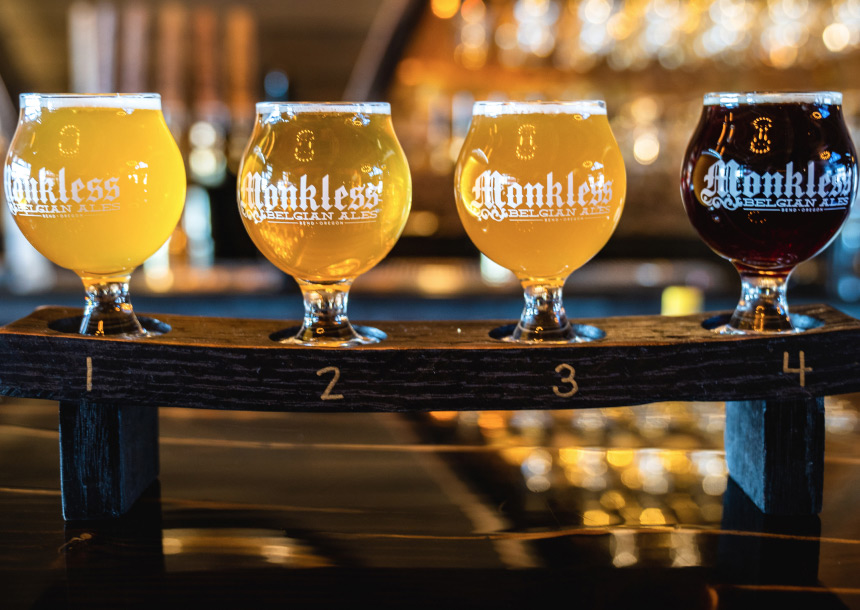 A wooden stand holds four Monkless Belgian Ale beers for tasting in Bend, Oregon