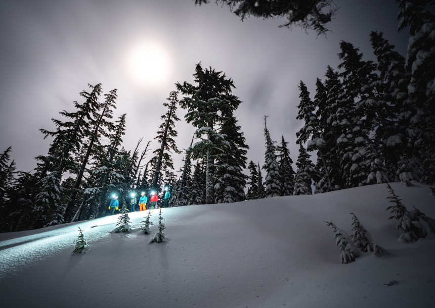 Five people in snow gear stand at the top of a snowy slope at dusk with lights on their ski helmets, with tall green trees in the background in Bend, Oregon
