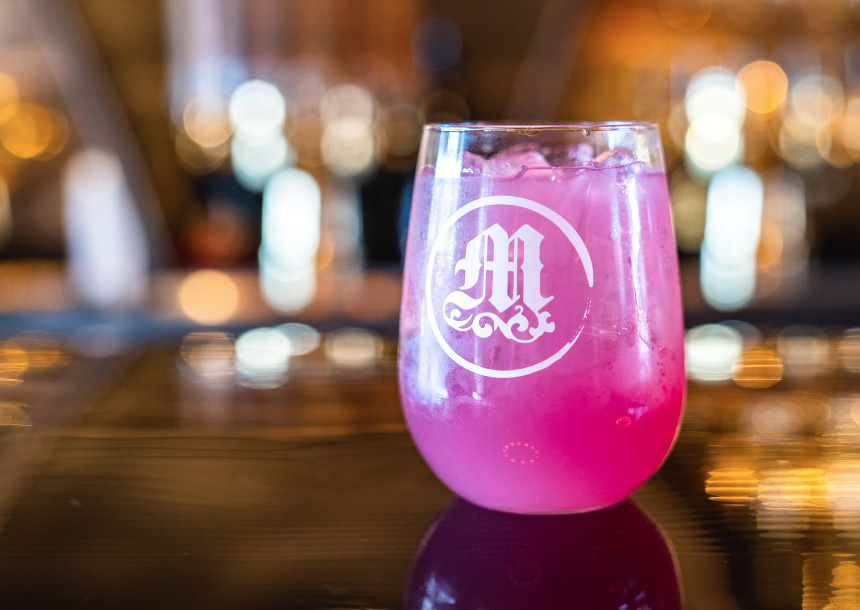 A bright pink cocktail in a stemless wine glass sits on a wooden table in Bend, Oregon