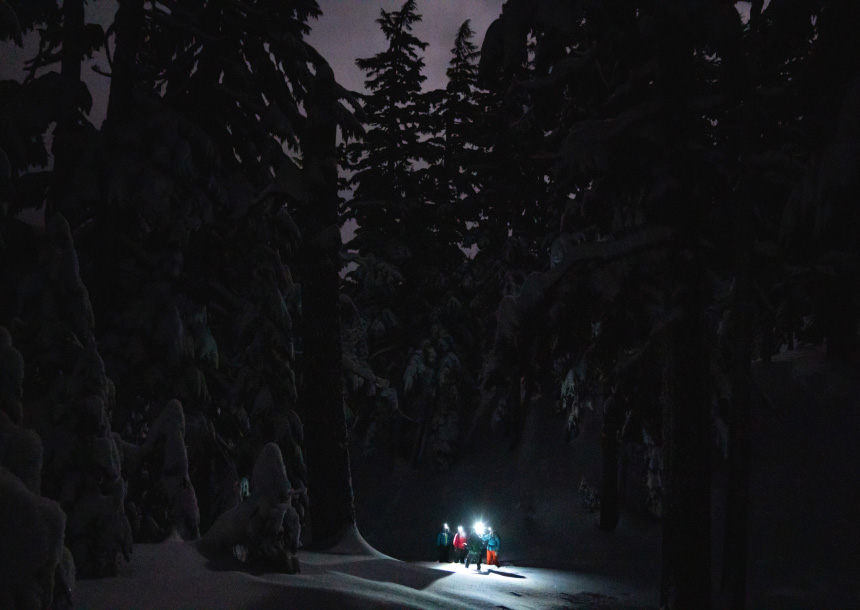 Four adults in snow gear with lights on their helmets stand in the snow surrounded by tall green trees after dark in Bend, Oregon