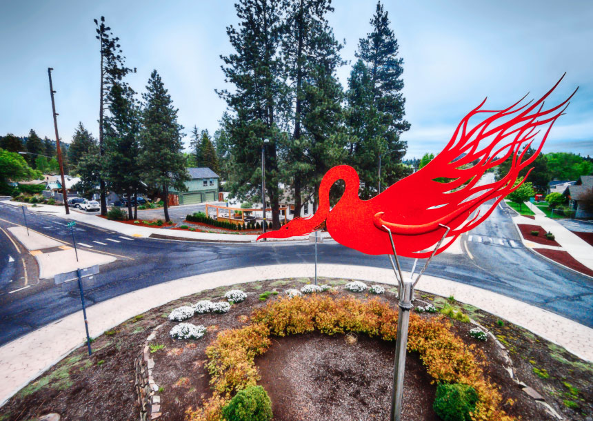 A red metal bird sculpture sits on a tall metal pole in a street roundabout in Bend, Oregon