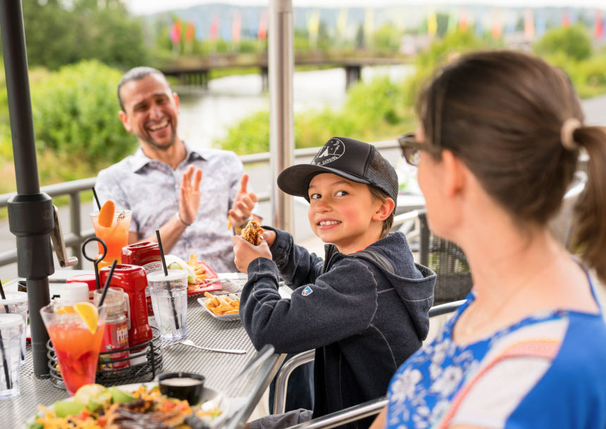 Seated at an outdoors table, a boy holding food smiles at a woman while a man in the background laughs and claps his hands in Bend, Oregon