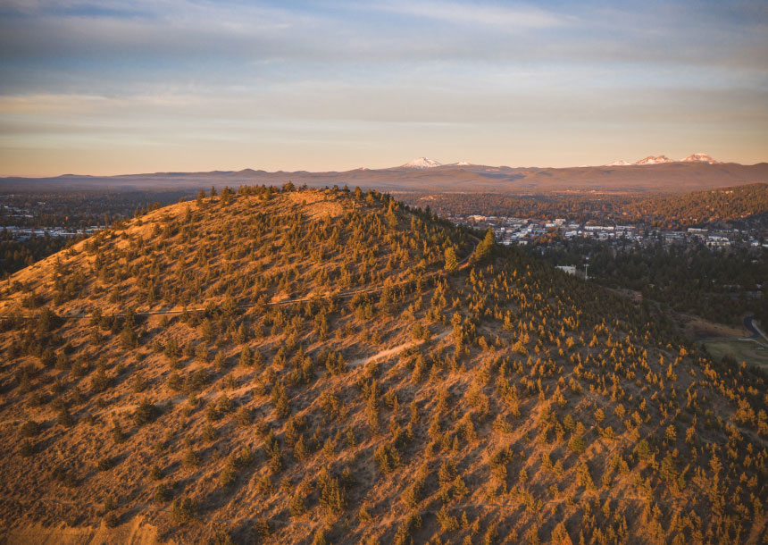 A large hill with trees overlooks Bend, Oregon