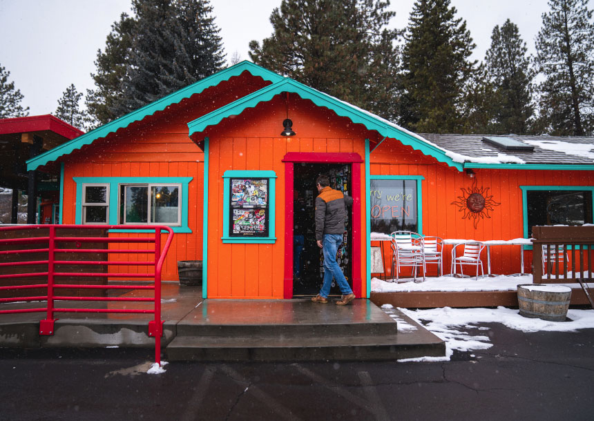 A man wearing jeans and a jacket enters an orange building in Bend, Oregon
